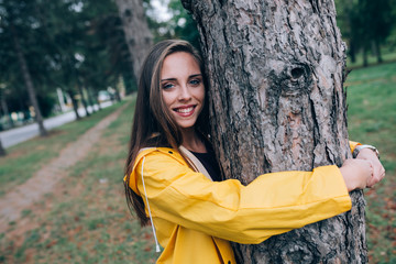 young woman in yellow raincoat outdoor in park