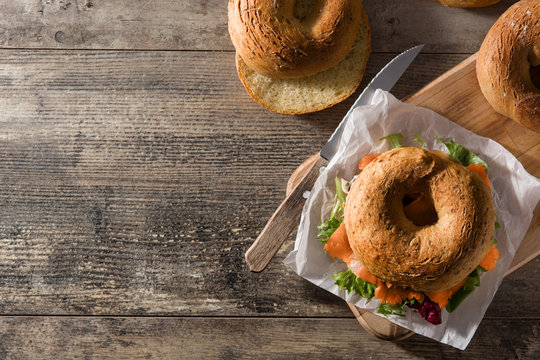 Bagel sandwich with cream cheese, smoked salmon and vegetables on wooden table. Copy space