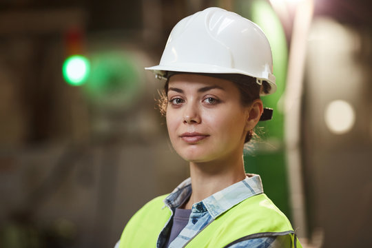 Portrait of young businesswoman in workwear looking at camera while standing in the plant