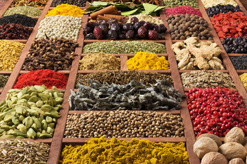 Fototapete - Spices and herbs in wooden trays, top view. Seasonings for cooking delicious food. Flavorings as background.
