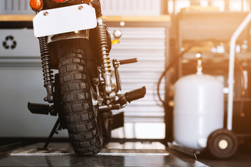 the rear of the classic motorcycles standing in repair shop with soft-focus and over light in the background