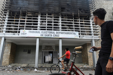 Residents take pictures of the building of the Santa Cruz Electoral Tribunal, which was set alight by demonstrators during a protest, in Santa Cruz