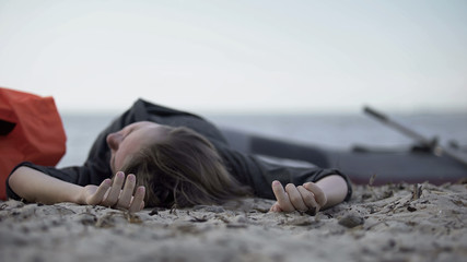 Unconscious woman lying on seashore, drowned swimmer, victim of shipwreck Fototapete