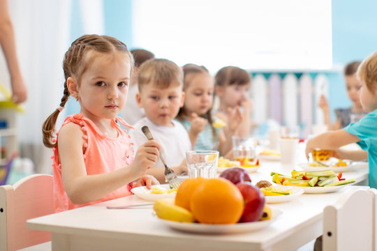 Kids have lunch in daycare. Children eat healthy food in kindergarten