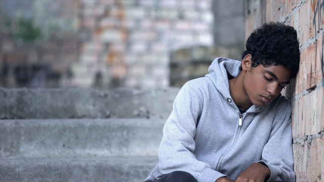 Depressed male teenager leaning brick wall sitting stairs, domestic violence