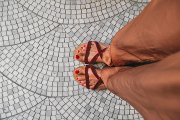 Legs of a Woman Standing on Floor with Tile Ornaments