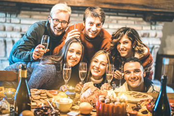 Happy friends on group photo selfie celebrating Christmas time with champagne and sweets food at dinner reunion party - Winter holiday concept with people having fun eating together - Warm filter