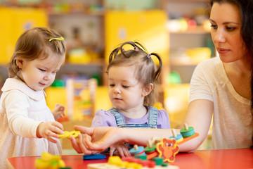 Children and nursery teacher play with toys in kindergarten playroom