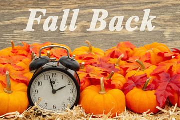 Fall Back time change message with a retro alarm clock with pumpkins and fall leaves