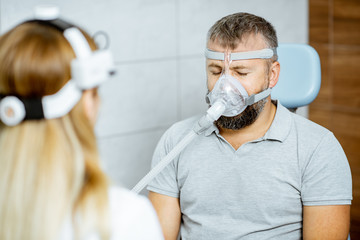 Adult man during a medical breathing treatment with respiratory mask against snoring sitting with doctor at the ENT office