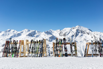 OBERGURGL, AUSTRIA - FEB 19, 2017: A line of skis and snowboards stored on racks outside a cafe on the slopes at Hochgurgl with the Otztal Alps in the background.