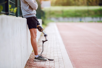 Cut out picture of handsome caucasian sporty handicapped man in sportswear and with artificial leg leaning on fence while holding arms crossed.