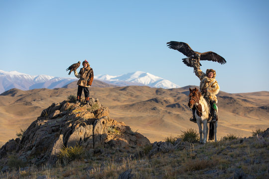 Two old traditional kazakh eagle hunters posing with their golden eagle in the mountains. Ulgii, Western Mongolia.