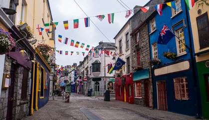 Tuinposter Smal steegje View of the main high street in Galway City with the brightly painted buildings and cobblestone streets on a cloudy day