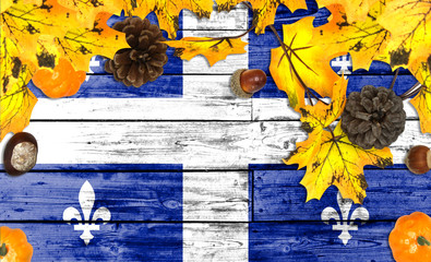 Quebec flag on autumn wooden background with leaves and good place for your text