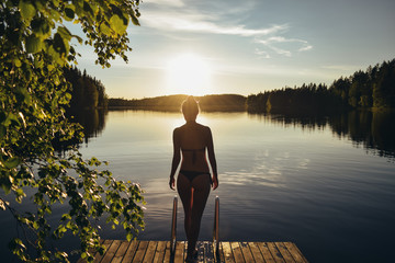 Young woman going into the lake from pier at sunset after sauna in Finland