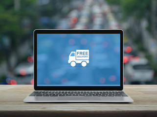 Free delivery truck flat icon with modern laptop computer on wooden table over blur of rush hour with cars and road in city, Business transportation online concept