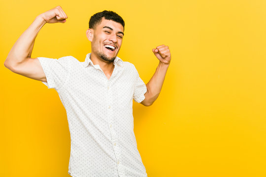 Young hispanic man raising fist after a victory, winner concept.