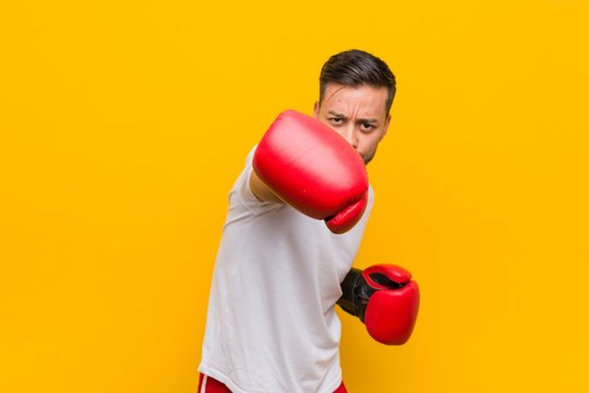 Young south-asian boxer man wearing red gloves.