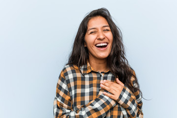 Young cool indian woman laughing keeping hands on heart, concept of happiness.