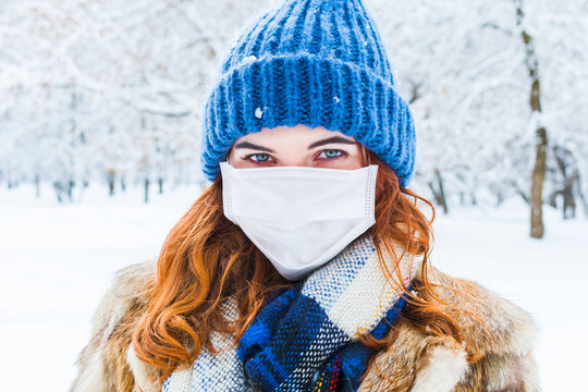 young woman in protective mask in winter in outdoors