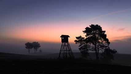 Poster de jardin Chasse Silhouette of a hunting tower at dawn.