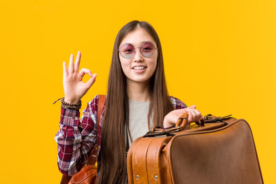 Young asian woman holding a suitcase cheerful and confident showing ok gesture.