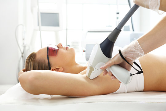 Laser hair removal under the arms. Smooth skin without hair. Woman in a laser hair removal salon