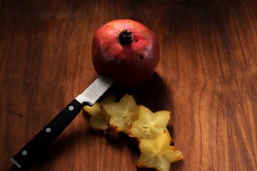 pomegranate, sliced star fruit and knife on dark wooden board