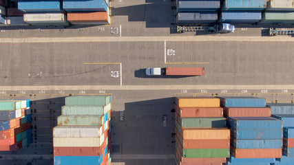 TOP DOWN: White truck transports a red freight container across the busy port. Wall mural