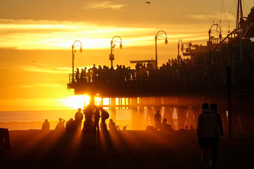 CLOSE UP: Tourists visit the famous Santa Monica beach and pier at sunset.