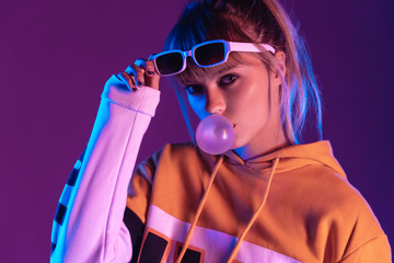 Stylish pretty young 20s fashion teen girl model wear glasses blowing bubble gum looking at camera standing at purple studio background, igen teenager in trendy night glow 80s 90s concept, portrait Wall mural