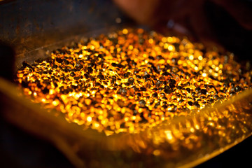 closeup picture of many ingots of melt gold, hot shiny metal pieces glowing