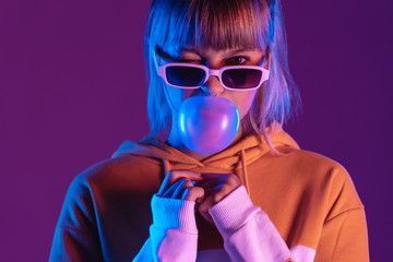 Stylish pretty young 20s fashion teen girl model wear glasses blowing bubble gum winking looking at camera stand at purple studio background, igen teenager in trendy light 80s 90s concept, portrait Wall mural