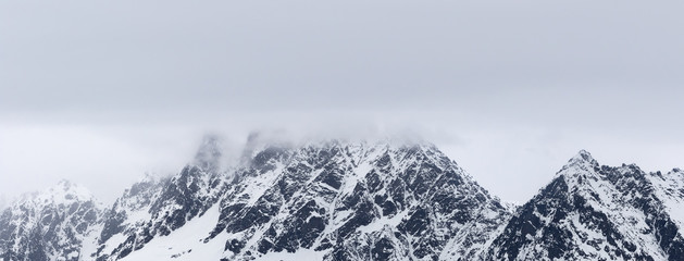Fototapete - Rocky mountains in snow and overcast grey sky at winter