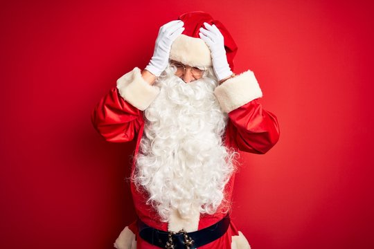 Middle age handsome man wearing Santa costume standing over isolated red background suffering from headache desperate and stressed because pain and migraine. Hands on head.