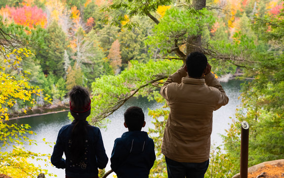 Dad and kids enjoying the view of Jack lake and the woods in Trail 5, Hemlock Bluff Trail in Algonquin Provincial Park.