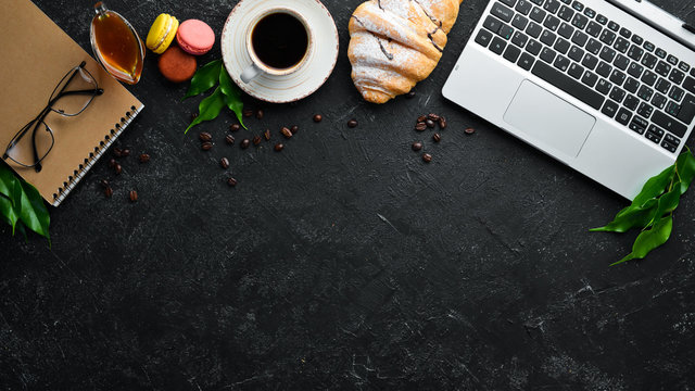 Laptop, coffee and croissant. Breakfast. On a black stone background. Top view. Free space for your text.