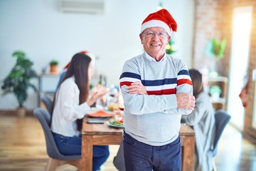 Senior handsome man smiling happy and confident. Standing wearing santa hat celebrating Christmas...
