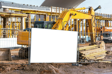 yellow excavator working on dirty construction site steel fence white mock-up