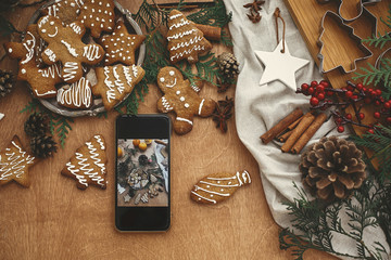 Phone with christmas photo of festive gingerbread cookies flat lay, anise, cinnamon, pine cones, cedar branches on rustic table. Merry Christmas. Holiday workshop