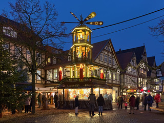 Celle, Germany. Christmas pyramid at Robert-Meyer-Platz and picturesque half-timbered houses at Poststrasse with Christmas illumination in Old Town in twilight.
