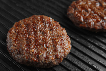 Prepared meat cutlets for burger on grill, closeup