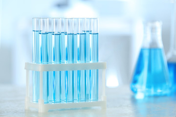 Fototapete - Test tubes with light blue liquid on table in laboratory