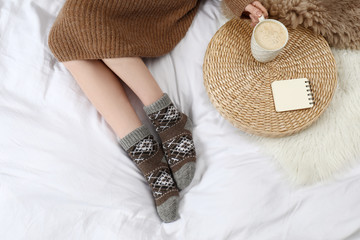 Fototapete - Woman with cup of hot drink wearing knitted socks on white fabric, top view. Warm clothes