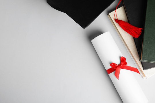 Graduation hat, books and student's diploma white background, top view. Space for text