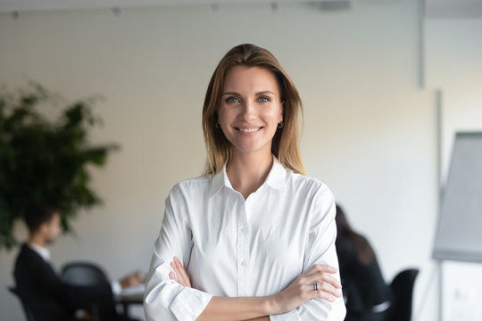 Smiling female professional manager standing arms crossed looking at camera