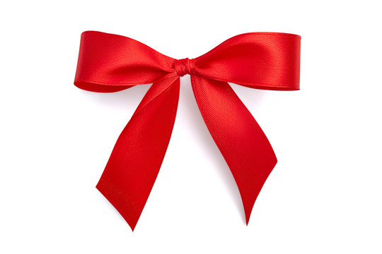 Flat lay simple holiday gift bow made of bright red shiny satin ribbon with a light gray soft shadow isolated on white background