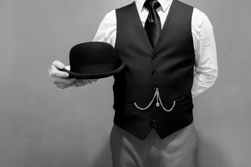 Butler Standing at Attention and Holding a Bowler Hat