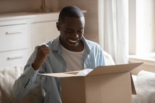 Excited african ethnicity smiling guy satisfied with fast easy delivery.